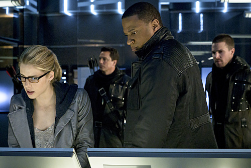 "Arrow -- ""My Name is Oliver Queen"" -- Image AR323B_0009b -- Pictured (L-R): Emily Bett Rickards as Felicity Smoak, John Barrowman as Malcolm Merlyn, David Ramsey as John Diggle and Stephen Amell as Oliver Queen -- Photo: Liane Hentscher/The CW -- © 2015 The CW Network, LLC. All Rights Reserved."